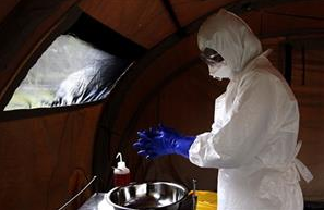 Nurse Dalila Martinez, trainer of the Cuban medical team to travel to Sierra Leone, washes her gloved hands during a practice drill at a training camp, in Havana   (Associated Press)