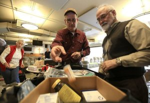The Rev. Chris Cooper (right) and Tom Baxter (center) pack supplies Wednesday for a short-term mission trip, while Betty Cooper (left) works on another bag. The medicine, vitamins and other supplies are destined for Cuba and should arrive there Friday.  Photo: Staton Breidenthal