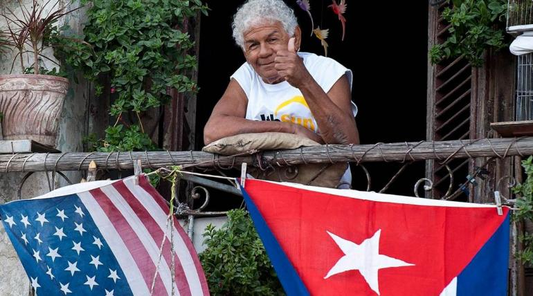 A Cuban gives the thumbs-up from his balcony decorated with U.S. and Cuban flags in Havana, on Jan. 16, 2015.   YAMIL LAGE / AFP - GETTY IMAGES
