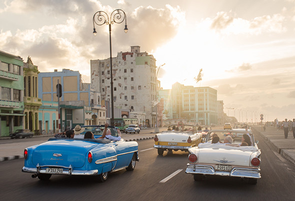 Locals drive 1950s-era American cars along the Malecón in Havana, Cuba. (Photograph by Erika Skogg)