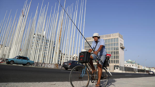 A fisherman cycles past the U.S. Interests Section building, behind right, in Havana in May. Desmond Boylan AP