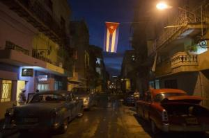 A Cuban national flag hangs over the street in downtown Havana, December 22, 2014. Reuters/Alexandre Meneghini