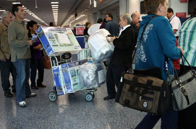 With goods like flat-screen high-definition television sets wrapped in plastic, passengers checked in last year for a charter flight to Cuba at Miami International Airport. Credit Chip Somodevilla/Getty Images