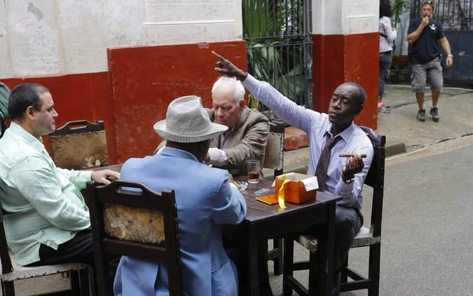 "The actor Don Cheadle, right, during a shoot for the series ""House of Lies"" outside a cafe in Havana. Credit Desmond Boylan/Associated Press"