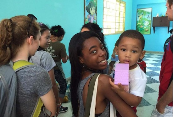 A student from St. Edmund Prep makes a new friend at a day care center in Cuba. Photo courtesy of St. Edmund Prep
